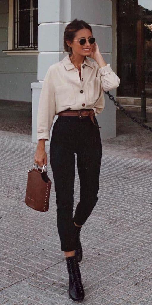 На девушке бежевая свободная рубашка с карманами и пуговицами, черные облегающие брюки длины ⅞, коричневая сумка в тон к ремню, черные ботинки на шнуровке и круглые очки.