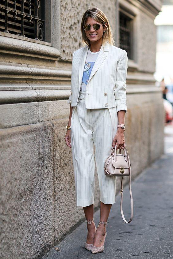Белый брючный костюм в полоску: укороченный жакет с пуговицами и брюки свободного кроя, бежевые туфли на каблуках с шнурками на щиколотке, нежно-розовая маленькая сумка и очки - стильный комфортный образ.