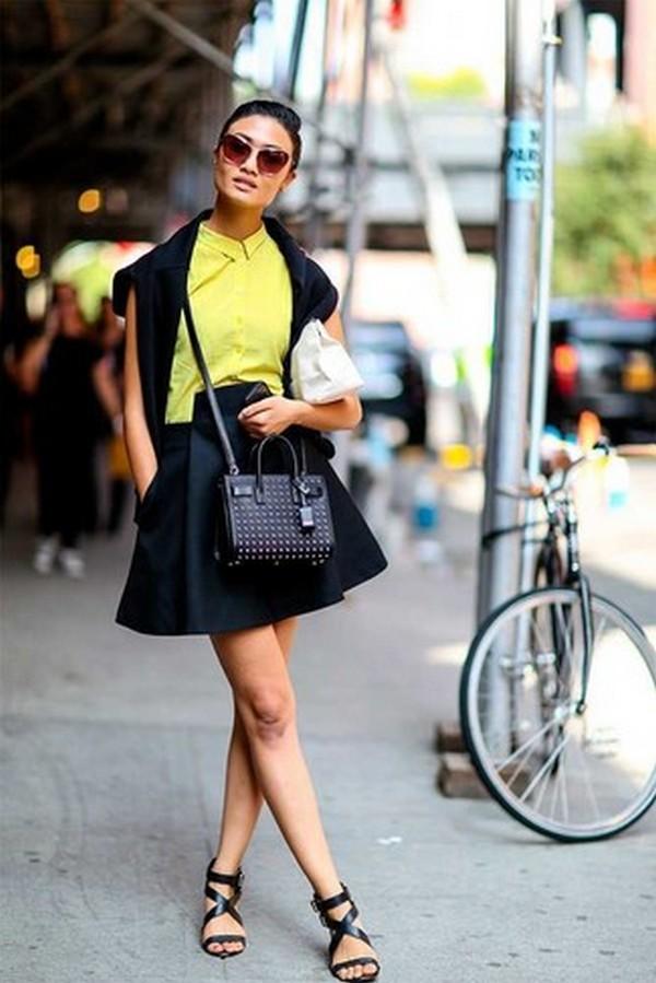 Желтая рубашка и короткая расклешенная юбка черного цвета в тандеме с босоножками и сумочкой – привлекательная капсула на каждый день