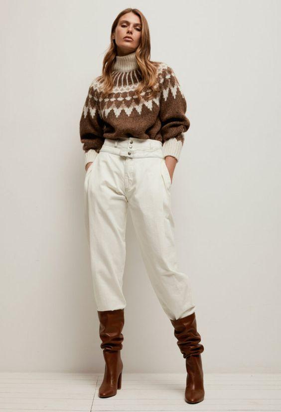На девушке коричневый вязаный свитер в скандинавском стиле с геометрическим орнаментом и объемными рукавами, белые джинсы свободного кроя с высокой посадкой и коричневые лаковые ботинки с толстым высоким каблуком.