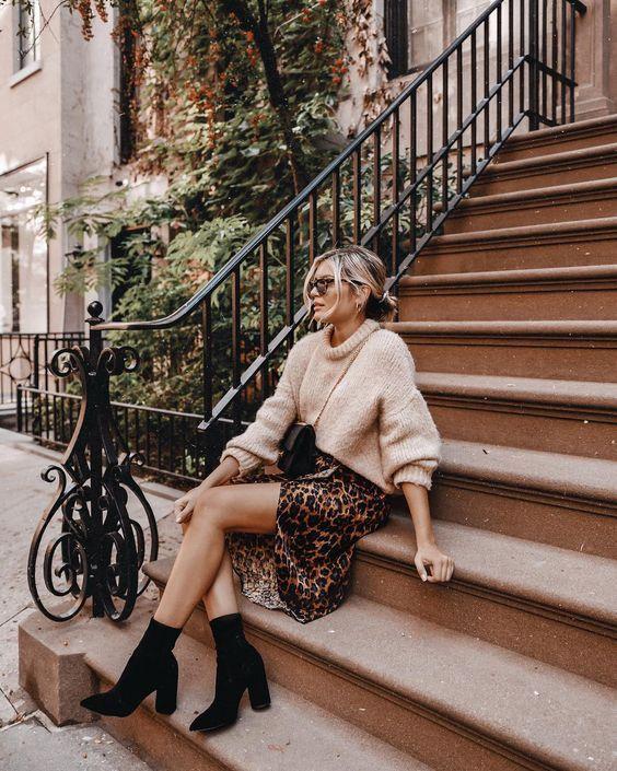 На девушке бежевый объемный свитер крупной вязки, свободная юбка-миди с анималистическим принтом и черные замшевые ботинки-носки на толстом каблуке. Образ дополняет поясная черная сумка и очки.