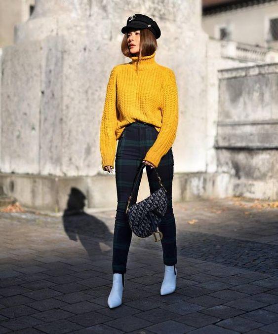 На девушке яркий желтый свитер крупной вязки с объемным горлом, облегающие брюки в крупную клетку, белые ботинки на каблуке и с заостренным носом, сумка асимметричной формы, черное кепи.