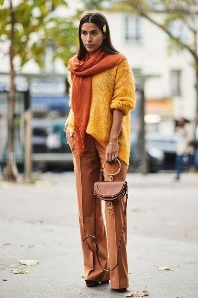 Желтый тонкий свитер оверсайз в сочетании с нюдовыми прямыми брюками-клеш, ботинками на каблуке и платформе, маленькой сумочкой и оранжевым шарфом.
