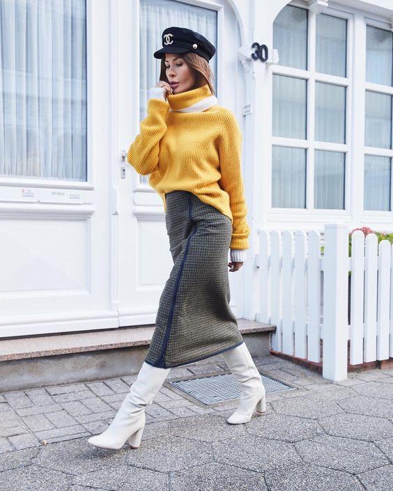 На девушке желтый свитер оверсайз с белыми манжетами, серая клетчатая юбка-карандаш длины миди, белые высокие сапоги на толстом каблуке, черное кепи.