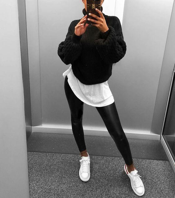 На девушке белая футболка, сверху черный свитер крупной вязки с объемными рукавами, кожаные черные леггинсы и белые кеды.