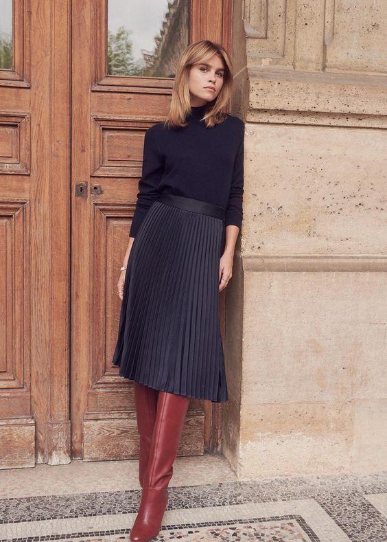 Черный тонкий свитер с горлом, заправленный в черную юбку-плиссе немного ниже колена, в сочетании с бордовыми кожаными ботфортами.
