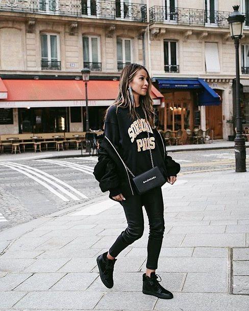 На девушке черный свитер оверсайз с надписью, объемный черный бомбер, черные кожаные леггинсы, ботинки на плоской подошве и поясная сумка.