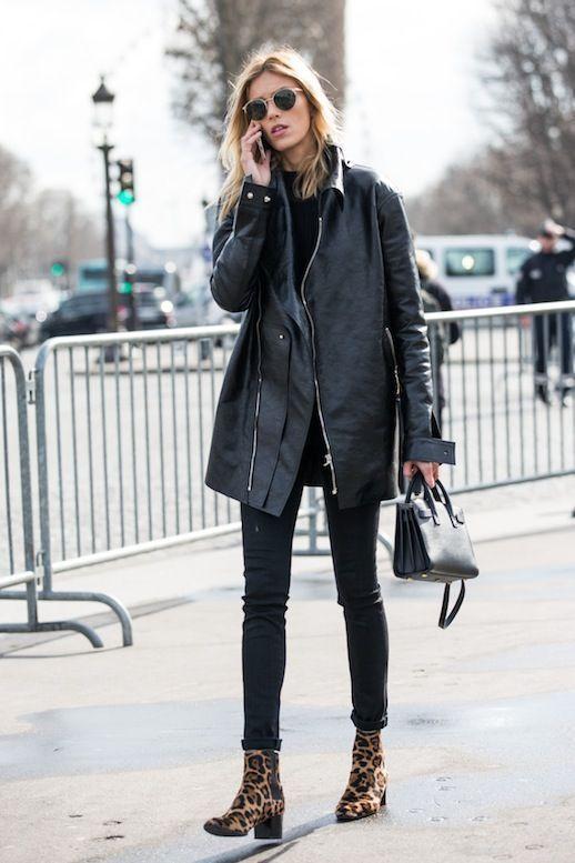Черный свитер в сочетании с черными скинни, кожаной курткой оверсайз, леопардовыми ботинками на толстом маленьком каблуке, кожаной черной сумкой и очками.