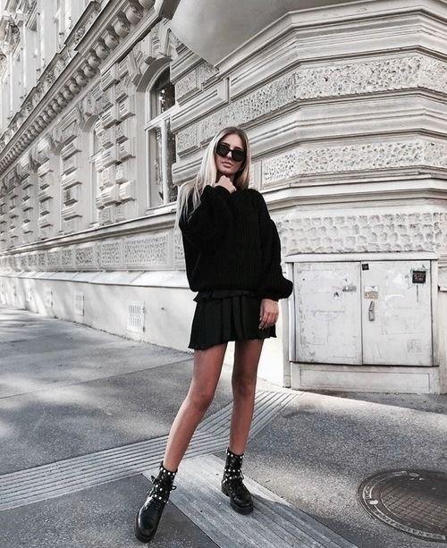 На девушке черный свитер оверсайз, черная юбка-мини в стиле преппи, тонкие черные колготки, ботинки на толстой подошве с ремешками и черные очки.