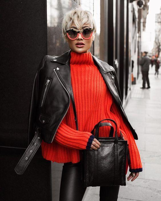 На девушке ярко-красный свитер крупной вязки, кожаные леггинсы, черная косуха, черная кожаная сумка и очки.