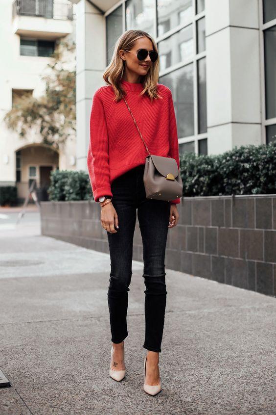 На девушке красный свитер, заправленный в черные скинни, бежевые лодочки на высоком каблуке с заостренным носом, поясная сумка и очки.