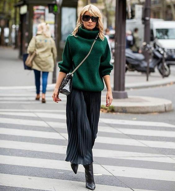 Девушка надела зеленый объемный свитер поверх легкого платья-плиссе длины миди, черные кожаные сапоги, очки и поясную сумку.
