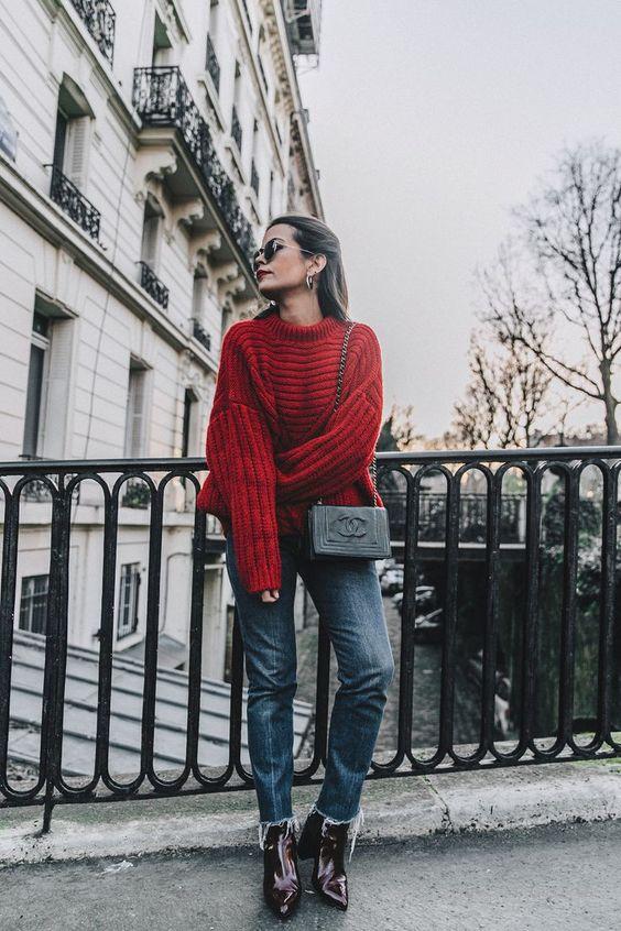 На девушке темно-красный объемный свитер крупной вязки, темно-синие прямые джинсы, лаковые ботинки с заостренным носом, поясная черная квадратная сумочка и очки.