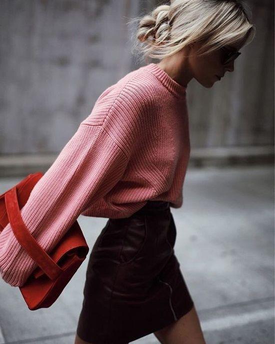 На девушке розовый свитер с объемными рукавами, бордовая юбка-карандаш длины мини с змейкой спереди, красная сумка.