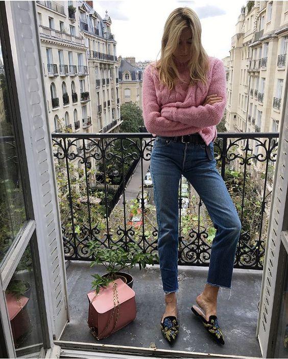 На девушке нежно-розовый укороченный свитер крупной вязки с ажурным узором, прямые синие джинсы средней посадки, черные мюли с заостренным носом и открытой пяткой, украшенные вышивкой, розовая кожаная сумка.