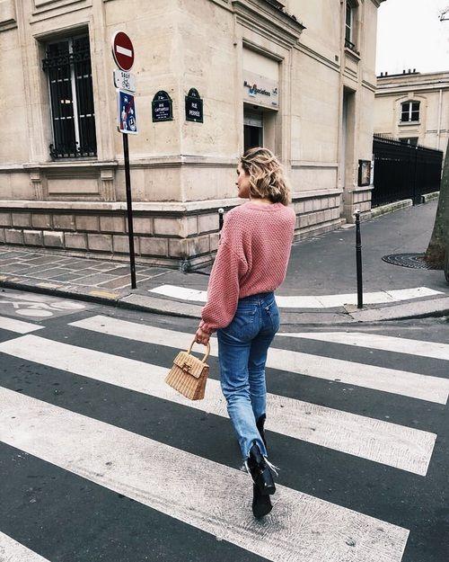 На девушке розовый объемный свитер, синие прямые джинсы, черные ботинки на толстой подошве и высоком каблуке, маленькая сумочка.