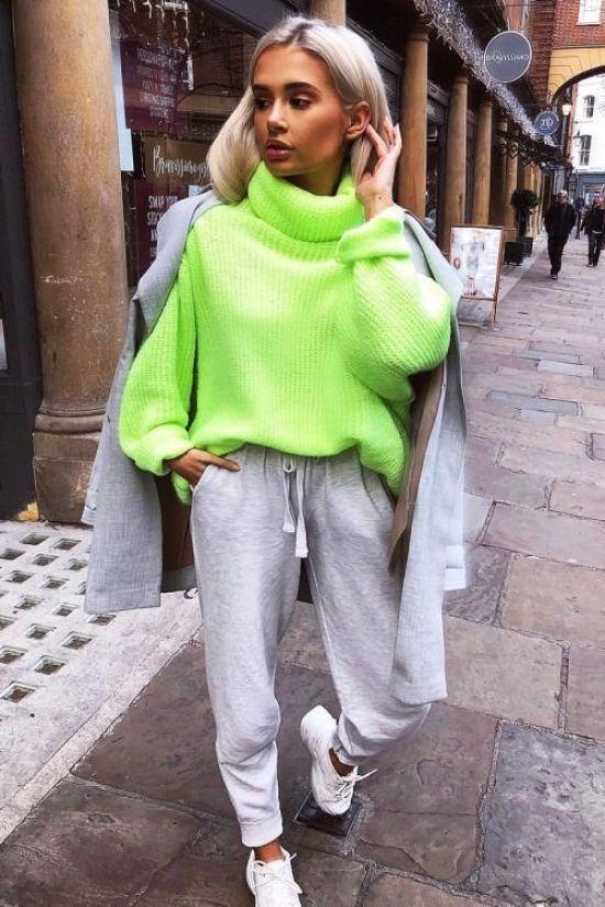 На девушке объемный ярко-зеленый свитер, спортивные серые штаны, пиджак оверсайз, белые кеды.