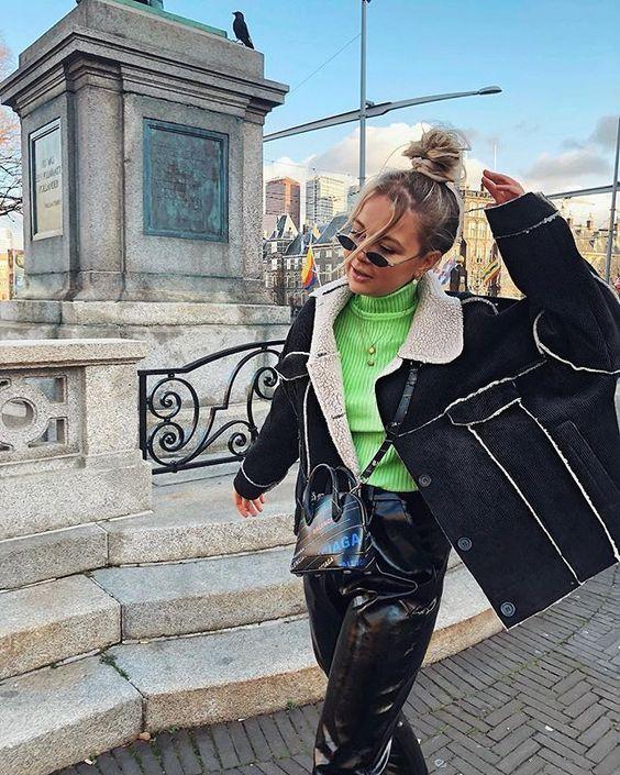 На девушке яркий зеленый облегающий свитер, кожаные свободные брюки, черная дубленка оверсайз, очки и поясная сумка.