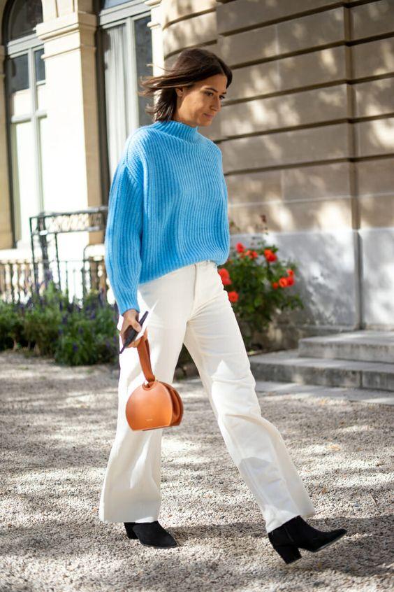На девушке ярко-голубой свитер, белые брюки свободного кроя, черные ботинки на каблуке и с заостренным носом, коричневая маленькая сумочка.