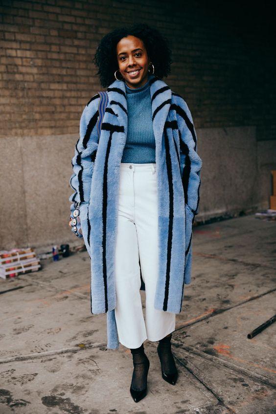 На девушке синий свитер, белые широкие джинсы, удлиненная синяя шуба с искусственного меха, черные лаковые лодочки, носки в сетку.