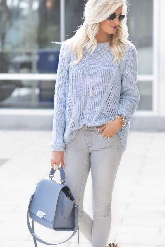 На девушке небесно-голубой свитер, серые джинсы средней посадки и голубая кожаная сумка. Образ дополнен аксессуарами.