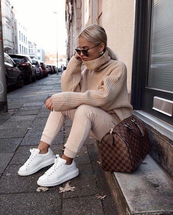 На девушке бежевый свитер оверсайз с горлом, такого же цвета спортивные облегающие штаны, белые кроссовки, большая сумка и очки.