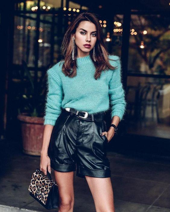 Голубой свитер, заправленный в черные кожаные шорты-бермуды, маленькая сумочка с леопардовым принтом.