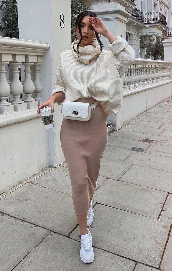 Белый объемный свитер с горлом, заправленный в бежевую трикотажную юбку-карандаш длины миди, белая маленькая поясная сумка и аккуратные кроссовки.