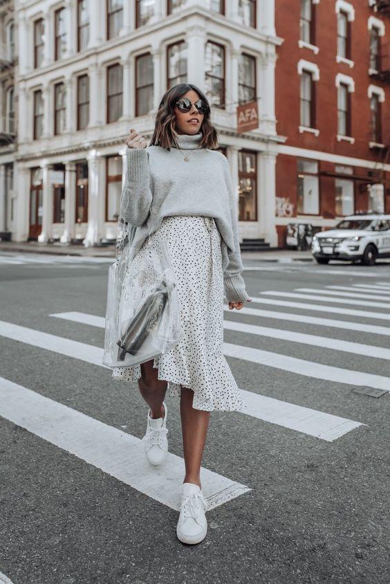 Серый свитер с горлом в сочетании со свободной белой юбкой в горошек и с воланами, белыми кедами и прозрачной пластиковой сумкой.