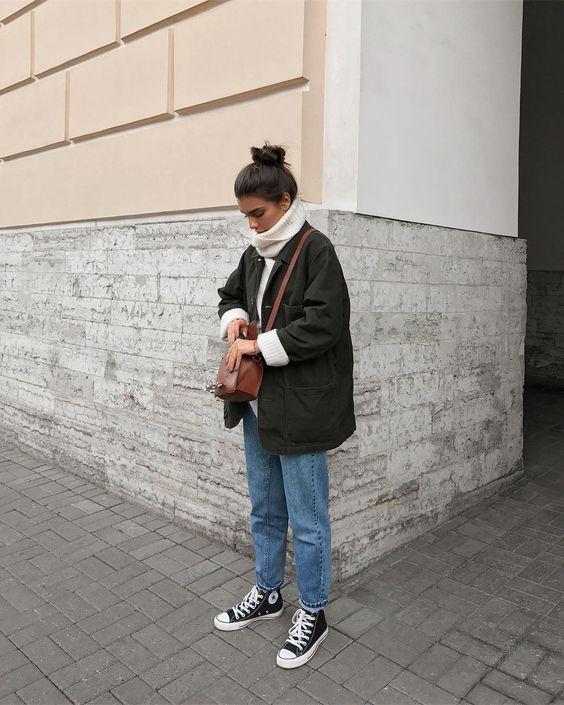 На девушке объемный белый свитер с горлом, прямые синие джинсы, темно-зеленый удлиненный бомбер, конверсы и коричневая поясная сумка из кожи.