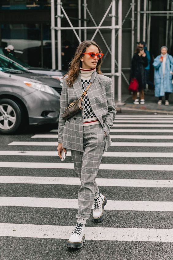 На девушке серый костюм с принтом гленчек: пиджак оверсайз и прямые брюки, клетчатый белый свитер с горлом, грубые белые ботинки на толстой подошве и шнуровке, маленькая поясная сумка и красные очки.