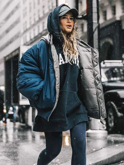 На девушке удлиненный синий свитер с капюшоном, объемная короткая куртка, синие леггинсы и кепка.