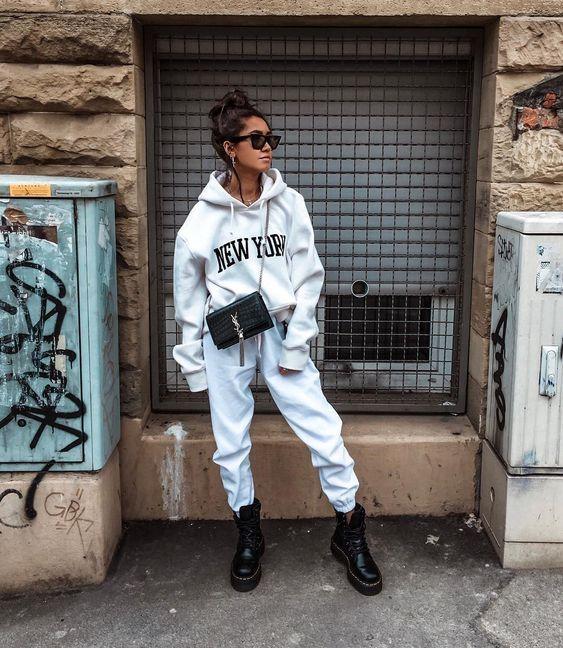 Белый укороченный свитер оверсайз с капюшоном и надписью в сочетании с белыми свободными спортивными штанами на манжетах, черными грубыми ботинками на толстой подошве и шнуровке, маленькой поясной сумкой и очками.