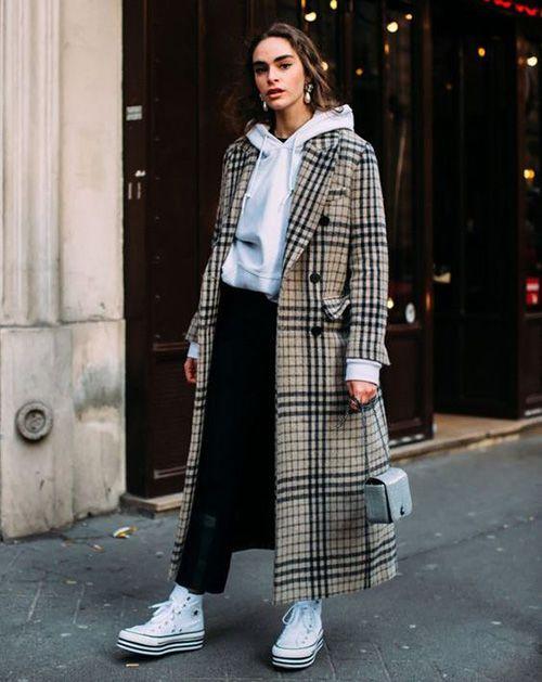 На девушке серый свитер с капюшоном, светло-коричневое пальто в клетку длины макси, черные джинсы, белые конверсы и маленькая сумка.