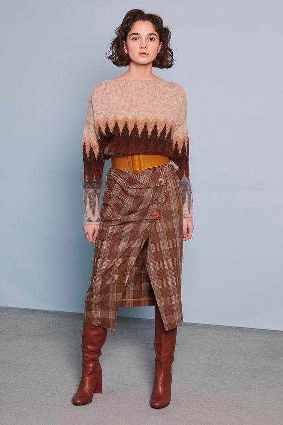 Бледно-коричневый свитер в сочетании с такого же цвета клетчатой юбкой-карандаш с горчичным поясом и разрезом, ковбойскими кожаными сапогами на каблуке.