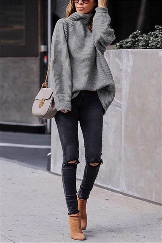 На девушке серый свитер оверсайз с хомутом, черные скинни и замшевые ботинки-носки на каблуке. Образ дополнен нежно-розовой поясной сумкой и очками.