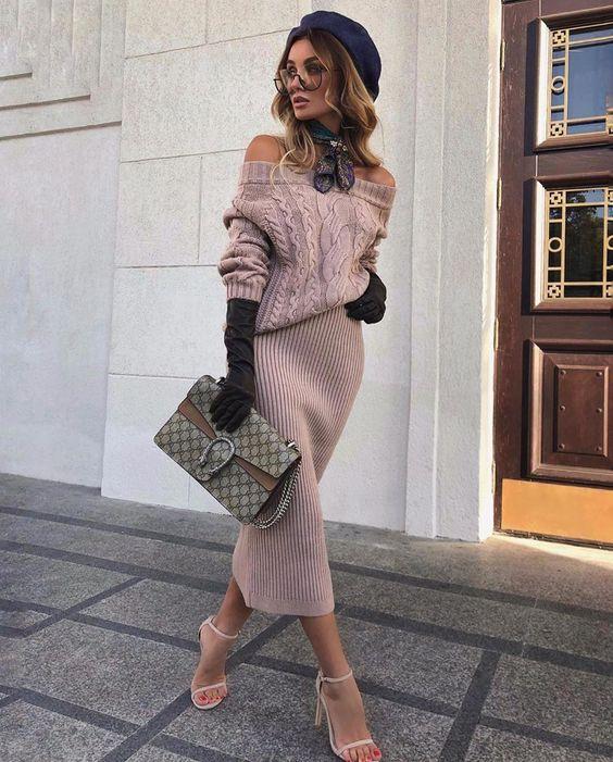 На девушке нежно-розовый трикотажный свитер с узорами и вырезом, такого же цвета трикотажная юбка-карандаш, босоножки на каблуке и аксессуары.