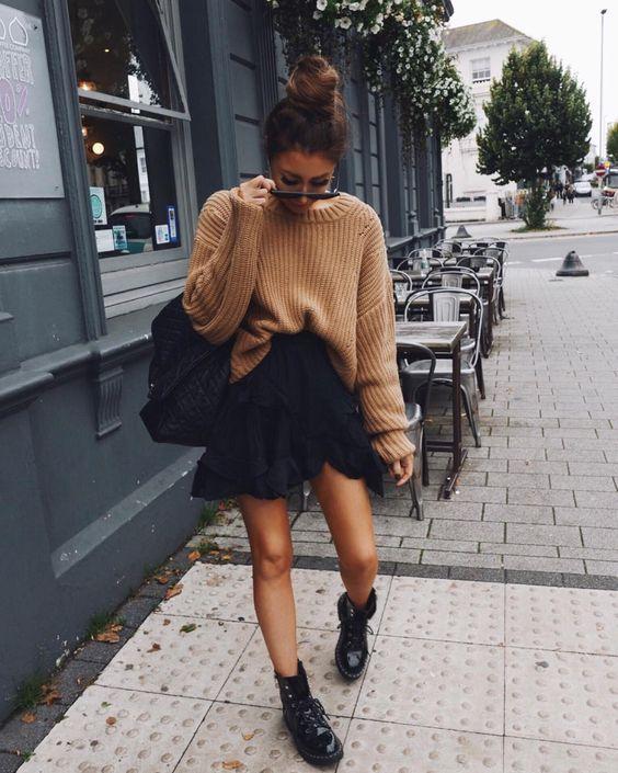 Девушка выбрала свитер оверсайз кофейного цвета, черную юбку-мини с воланами, грубые лаковые ботинки на толстой подошве и шнуровке, рюкзак и очки.