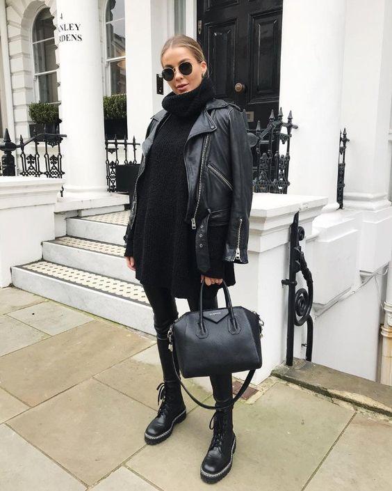 На девушке черный свитер оверсайз с объемным горлом, кожаные леггинсы, грубые ботинки на толстой подошве и шнуровке, кожаная большая сумка и черная куртка, круглые очки.
