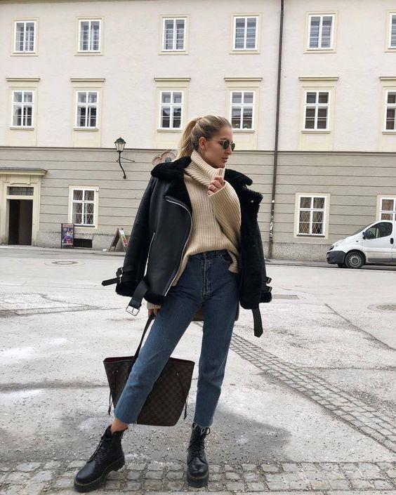 Бежевый свитер оверсайз с объемным воротником, прямые синие джинсы, грубые кожаные черные ботинки, объемная черная дубленка. Образ дополняет сумка и очки.