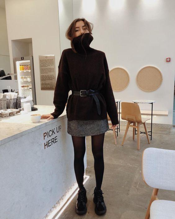 На девушке темно-коричневый свитер с объемным горлом, подчеркнутый черным кожаным поясом, прямая серая юбка-мини, черные колготы и кроссовки.