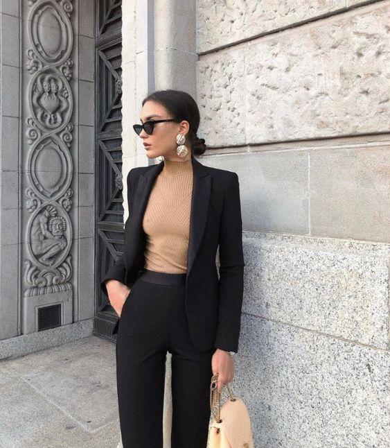 На девушке бежевый облегающий свитер с воротником, строгие прямые брюки и черный прямой пиджак. Образ дополнен аксессуарами.