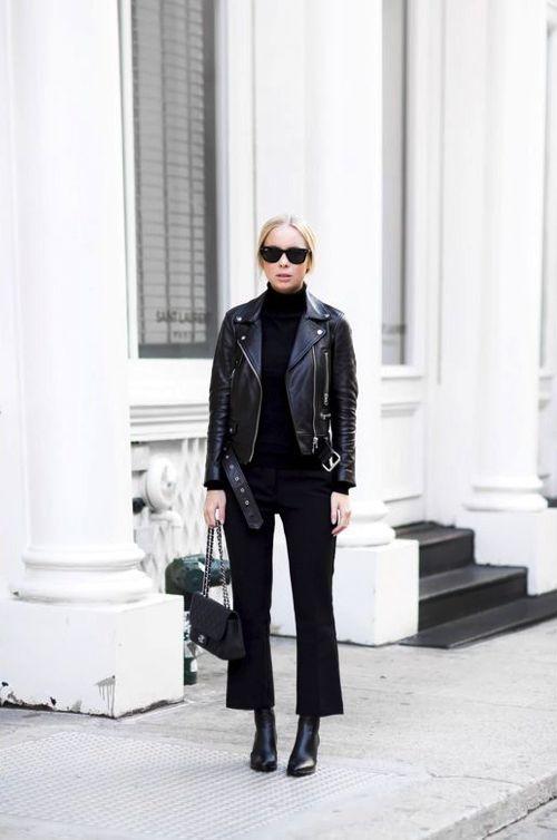 На девушке черный свитер с плотно облегающим воротником, черные прямые брюки, кожаная куртка и ботинки с заостренным носом, черная сумка и очки.