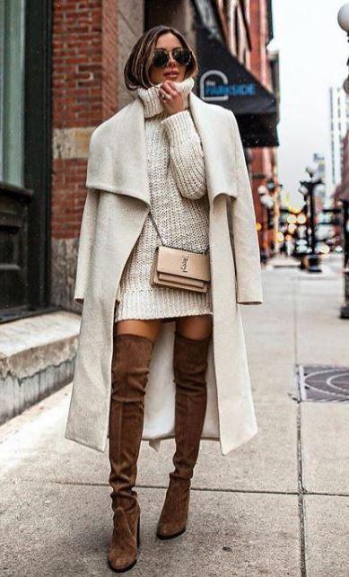 На девушке белый вязаный объемный свитер-платье с горлом, белое удлиненное пальто, замшевые коричневые высокие ботфорты. Образ дополняет маленькая поясная сумка и очки.