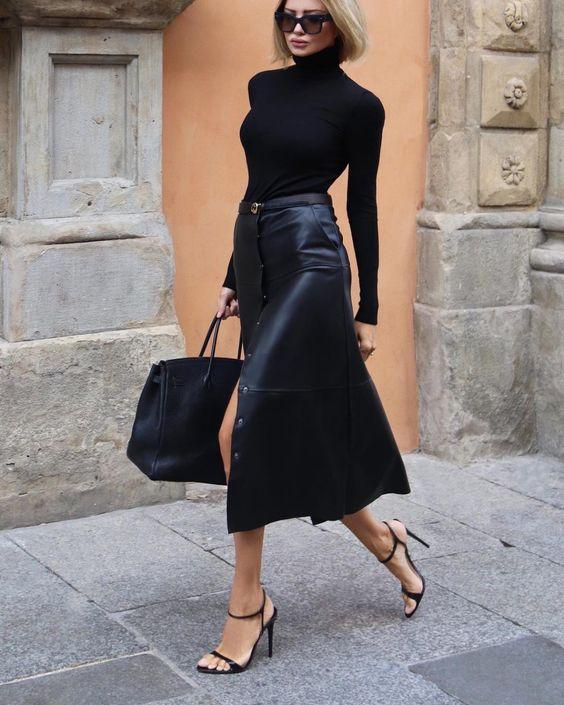 Черный облегающий свитер с горлом в сочетании с черной кожаной юбкой ниже колена и разрезом, босоножками на тонком каблуке, большой сумкой и очками.