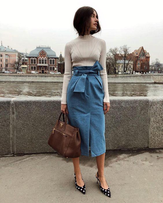 На девушке белый облегающий свитер, юбка-карандаш ниже колена из денима с поясом в виде банта, черные мюли в горошек с заостренным носом и открытой пяткой, коричневая большая сумка.