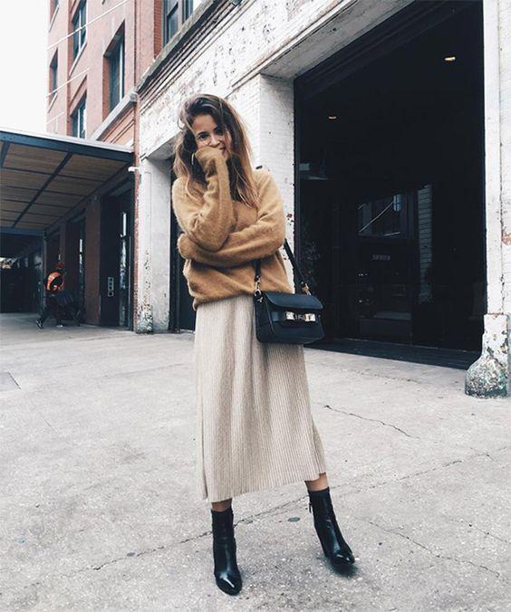 На девушке коричневый свитер и бежевое прямое платье длины миди, черные кожаные ботинки и поясная сумка.