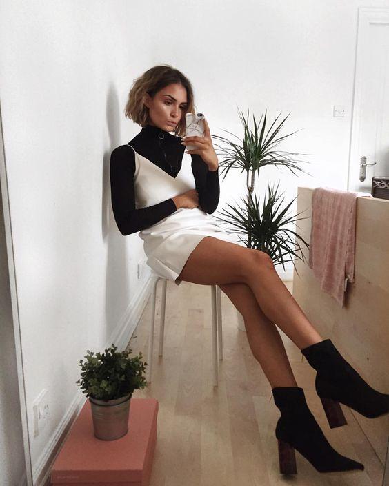 Девушка выбрала черный облегающий свитер с горлом и сверху надела белое платье-мини на бретелях, черные ботинки-носки с острым носом и на толстом каблуке.