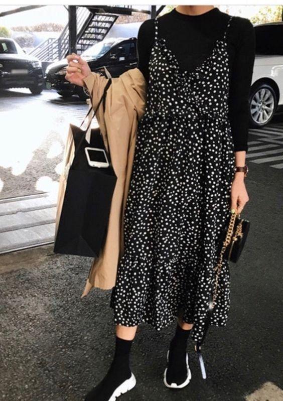 Черное платье в белый горошек длины миди  надетое поверх черного облегающего свитера, черные кроссовки Balenciaga, бежевый тренч и черная сумка.