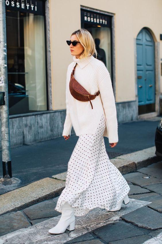 На девушке объемный белый свитер с горлом, белое платье в мелкий черный  горошек длины макси, белые сапоги на среднем толстом каблуке, коричневая кожаная поясная сумка и черные очки.